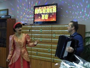 20 февраля 2018г. в15 час. в библиотеке им. В.В. Маяковского ЦБС г. Ярославля состоялся праздничный вечер, посвященный 80-летию библиотеки. Самые преданные друзья и почитатели библиотеки, коллеги, официальные гости пришли в этот день поздравить и поблагодарить ровесницу района, любимую библиотеку с юбилейной датой. Библиотекари празднично оформили внутреннее пространство библиотеки, подготовили интересные книжные выставки, динамичную и содержательную программу праздника. Внутриполочные выставки привлекают внимание читателей рассказом о наиболее современных и востребованных библиотечных проектах: Мастерская «Я САМ», «КиноСреда», «БиблиоСад», «Акулы пера» и самый новый проект «Ярославская кукла», возвращающий читателя к малоизученной и не сохранившейся в музеях тряпичной игровой ярославской кукле, сыгравшей огромную роль в культуре русского народа. Библиотека подобна кораблю, путешествующему во времени, сохраняющему драгоценный груз-фундамент, основы культуры -книги. Корабль, носящий звонкое сильное имя Владимира Маяковского, держит курс в будущее, принимая все вызовы времени. А время диктует новые требования. Мы пытаемся реализовать образ библиотеки- открытого творческого пространства, где любой человек получает доступ ко всей полноте знания, к наследию, воплощенному в книгах. Руководя читателями, давая им консультации, помогая им стать исследователями, мы помогаем воспитать человека-творца, растущего, ответственного за мир, радикально отличающегося от «квалифицированного потребителя», которому лишь бы «чай всегда пить», как говорил Ф.М. Достоевский. Праздник украсили песни в исполнении дуэта супругов Натальи и Сергея Невских (ДК «Гамма). В программе вечера знакомство с новой художественной выставкой нашего проекта «БиблиоВернисаж»- персональной выставкой ярославского художника Александра Ульянова. Дружба с семьей знаменитых ярославских художников началась более 10 лет назад, когда народный художник РФ Владимир Ульянов подарил библиотеке свою картину «Приезд Владимир